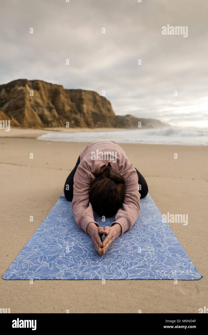 woman practicing yoga doing a child's pose at the beach - Stock Image