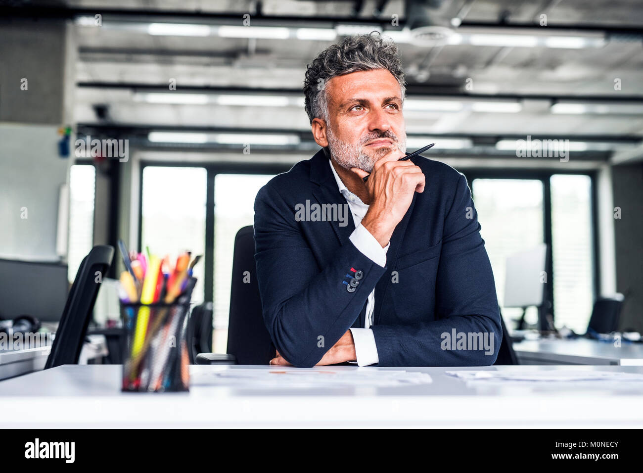 Confident mature businessman in office thinking - Stock Image