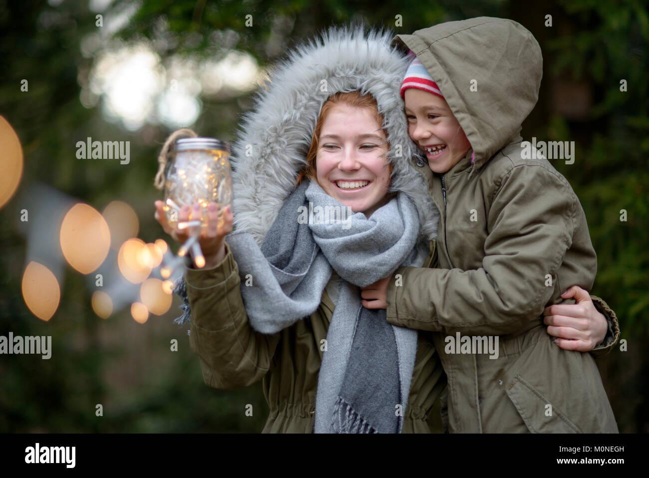 Mädchen mit funkelnden Lichterketten,  Licht im Glas, im Winter, Oberbayern, Bayern, Deutschland - Stock Image