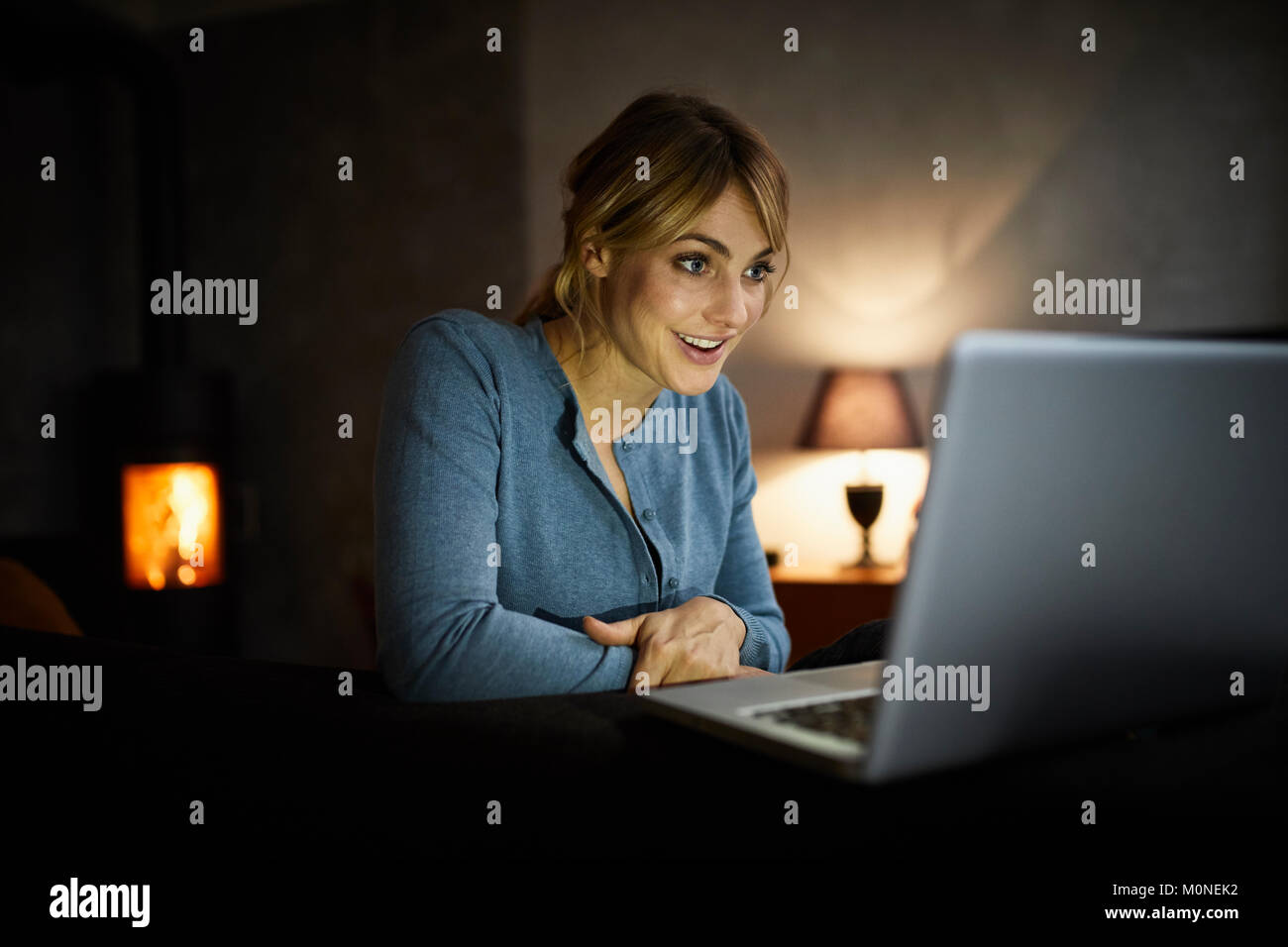 Portrait of amazed woman using laptop at home in the evening - Stock Image