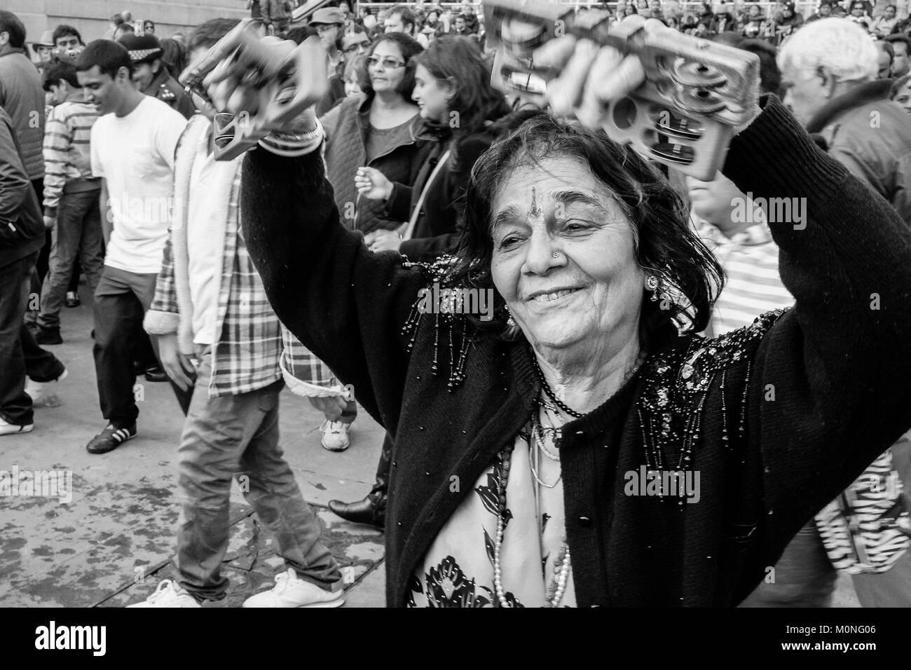 London black and white street photography indian woman dancing during diwali celebrations stock