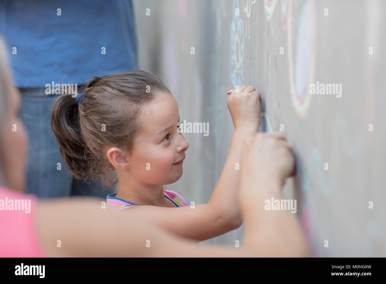 Girl drawing colourful pictures with chalk on a concrete wall - Stock Image