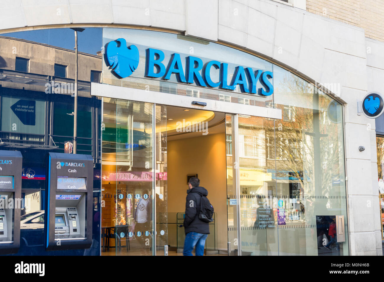 A person entering a Barclays bank branch on a High Street in England 2018, UK - Stock Image