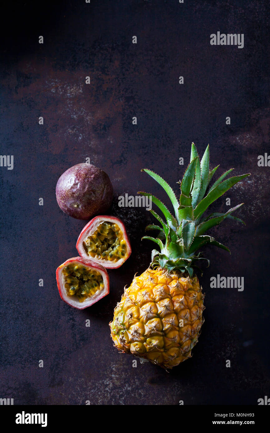 Baby pineapple and maracujas on rusty metal - Stock Image