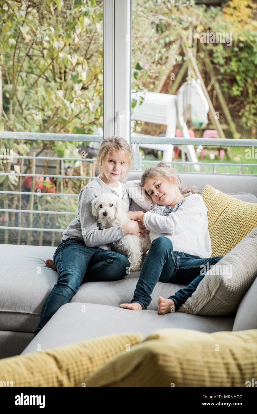 Portrait of two girls with dog on couch in living room Stock Photo