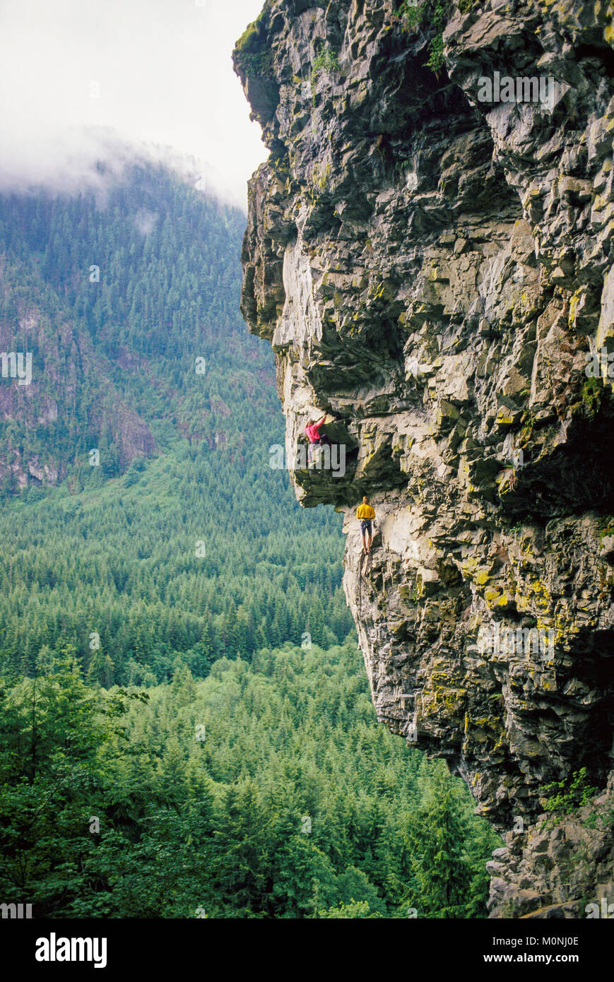 Two men climbing an overhanging cliff up the North Fork of the Snoqualmie River, Washington, USA. - Stock Image