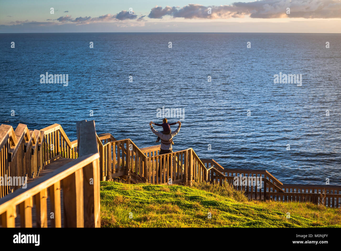 Father giving his son piggyback ride at Hallett Cove boardwalk while enjoying sunset, South Australia - Stock Image