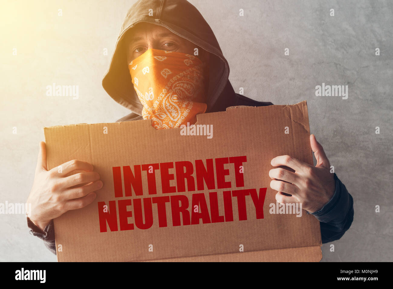 Hooded activist protestor holding Internet neutrality protest sign. Man with hoodie and scarf over face taking part - Stock Image