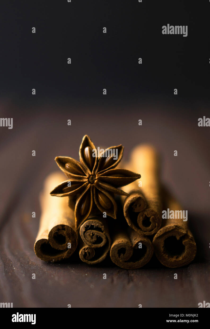 Creative concept photo of cinnamon sticks on wooden brown background. - Stock Image
