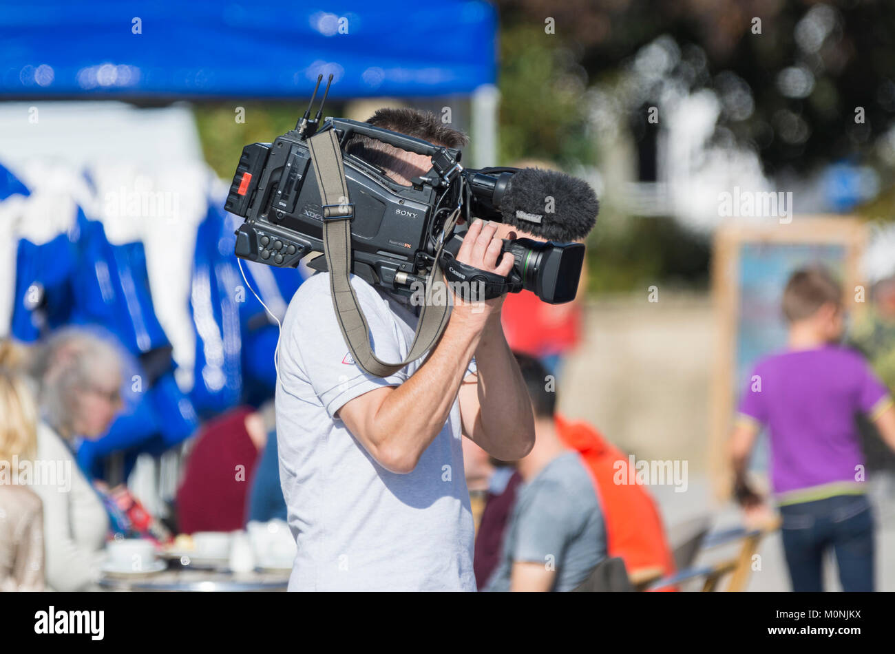 TV cameraman holding a professional Sony video camera for an outside broadcast in the UK. - Stock Image