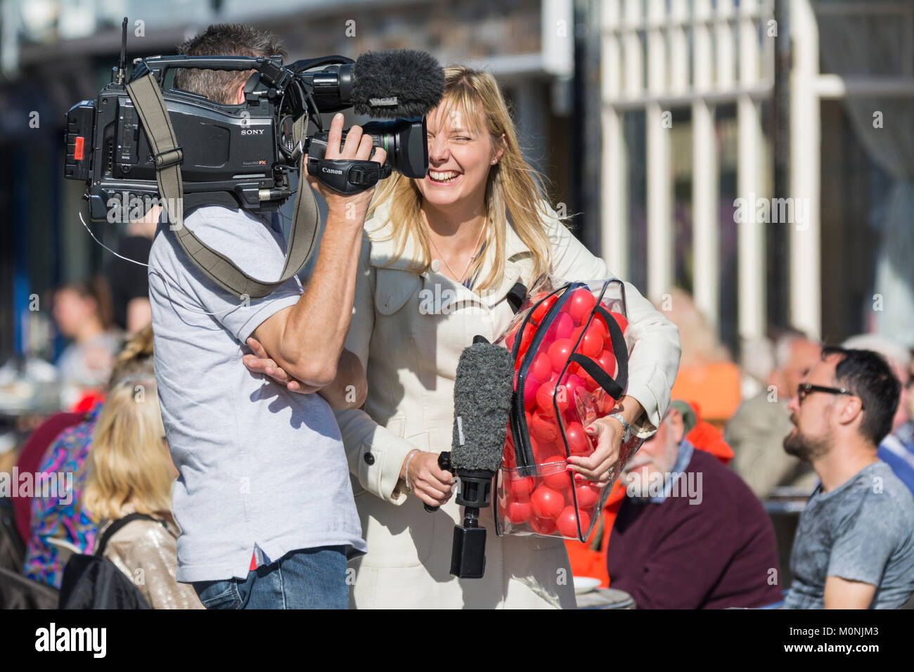 Female TV presenter laughing and smiling on the job, on an outside broadcast in the UK. - Stock Image
