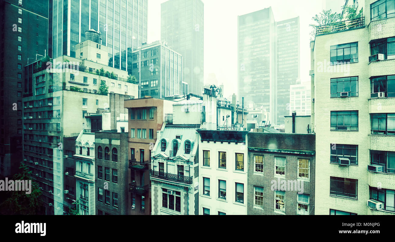 Vintage toned picture of old apartment buildings in Midtown Manhattan on a rainy day, New York, USA. Stock Photo
