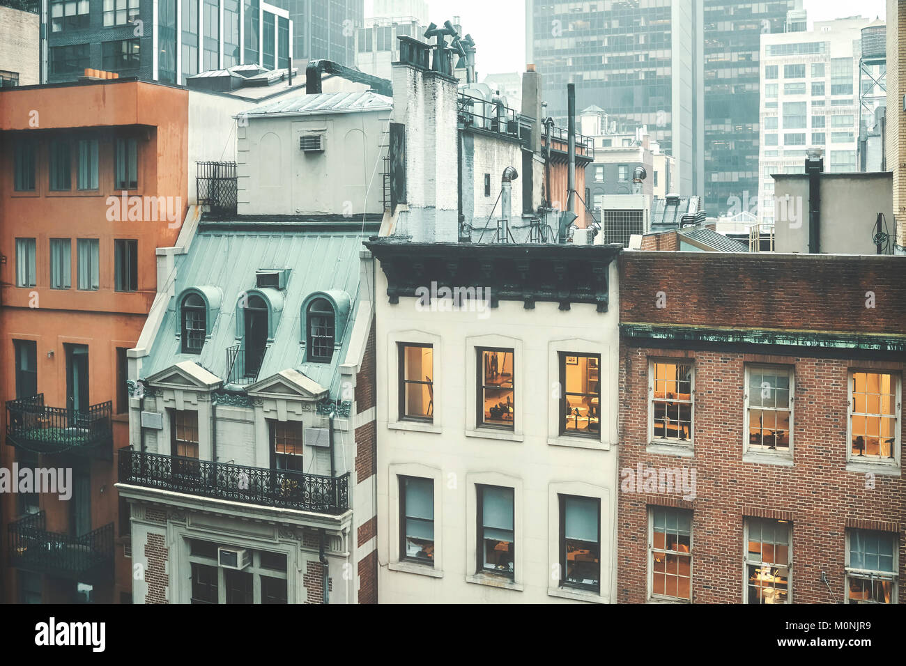 Retro toned picture of old buildings in Midtown Manhattan on a rainy day, New York, USA. - Stock Image