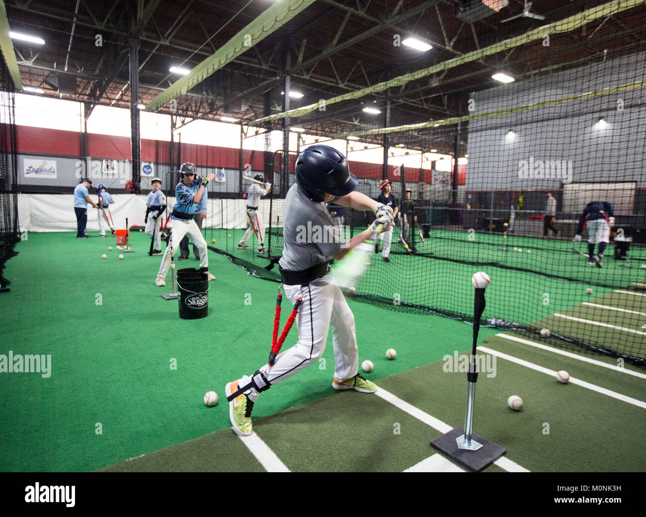 Batters hitting off a tee at a baseball training facility in New Jersey. - Stock Image