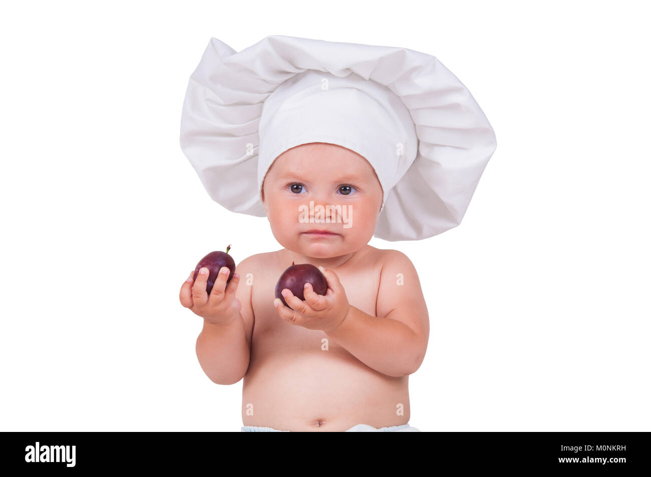 6262a2cbc A small child is eating plums in a chef suit on a white background ...