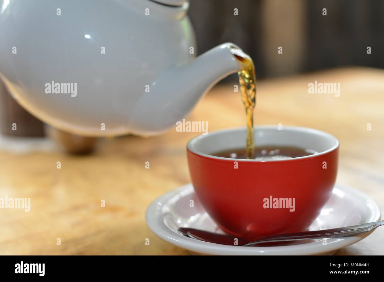 Black Tea Being Poured White Ceramic Teapot Into A Red Cup With White Stock Photo Alamy