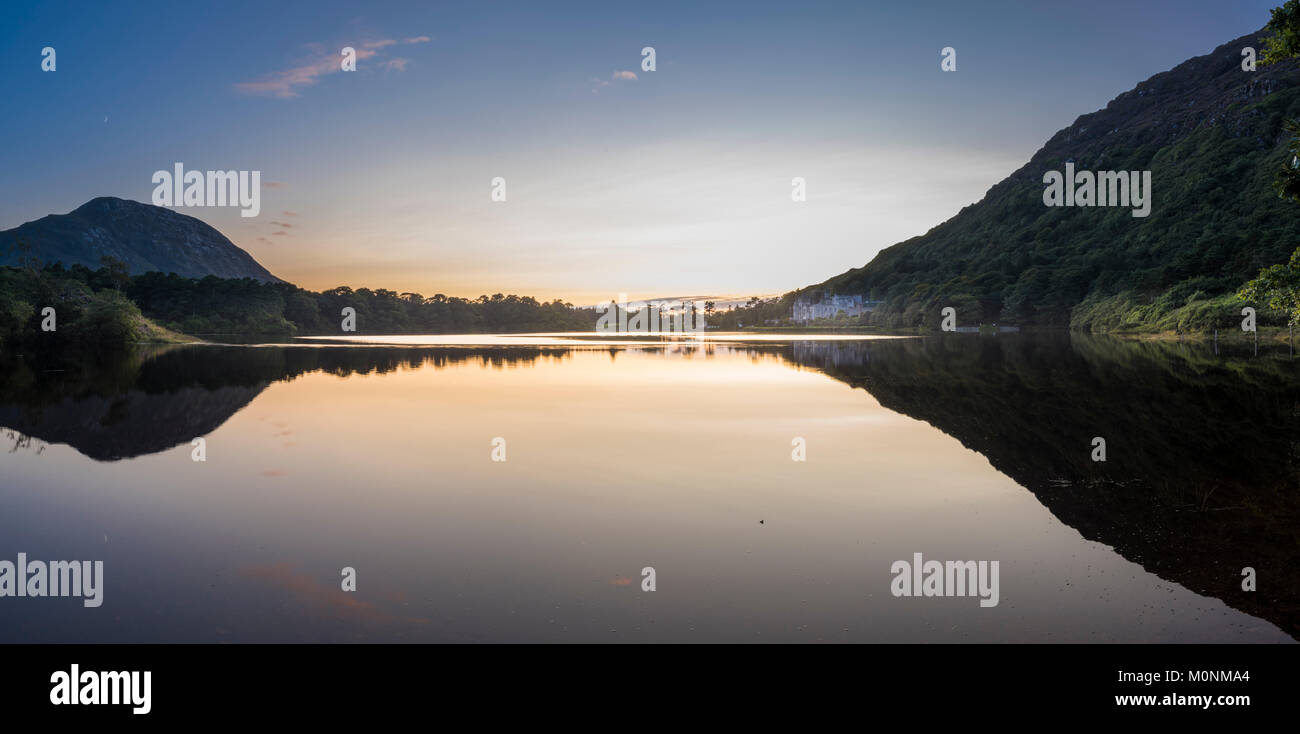 Pollacappul Lake, Connemara, County Galway, is almost perfectly still after sunset with perfect reflection and Kylemore - Stock Image