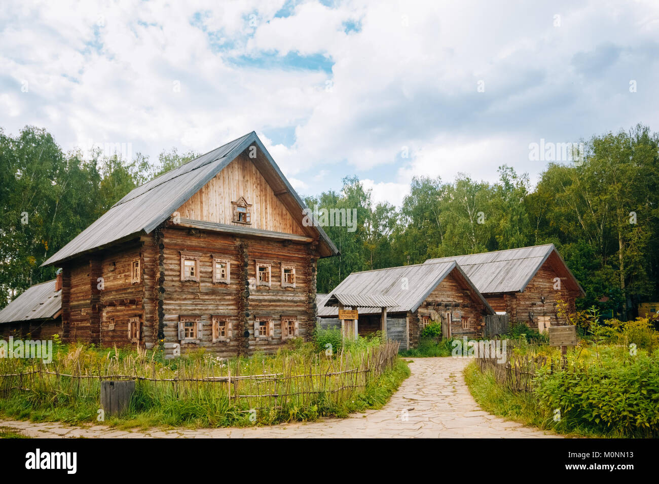 Wooden house and other buildings of wood near the forest. - Stock Image