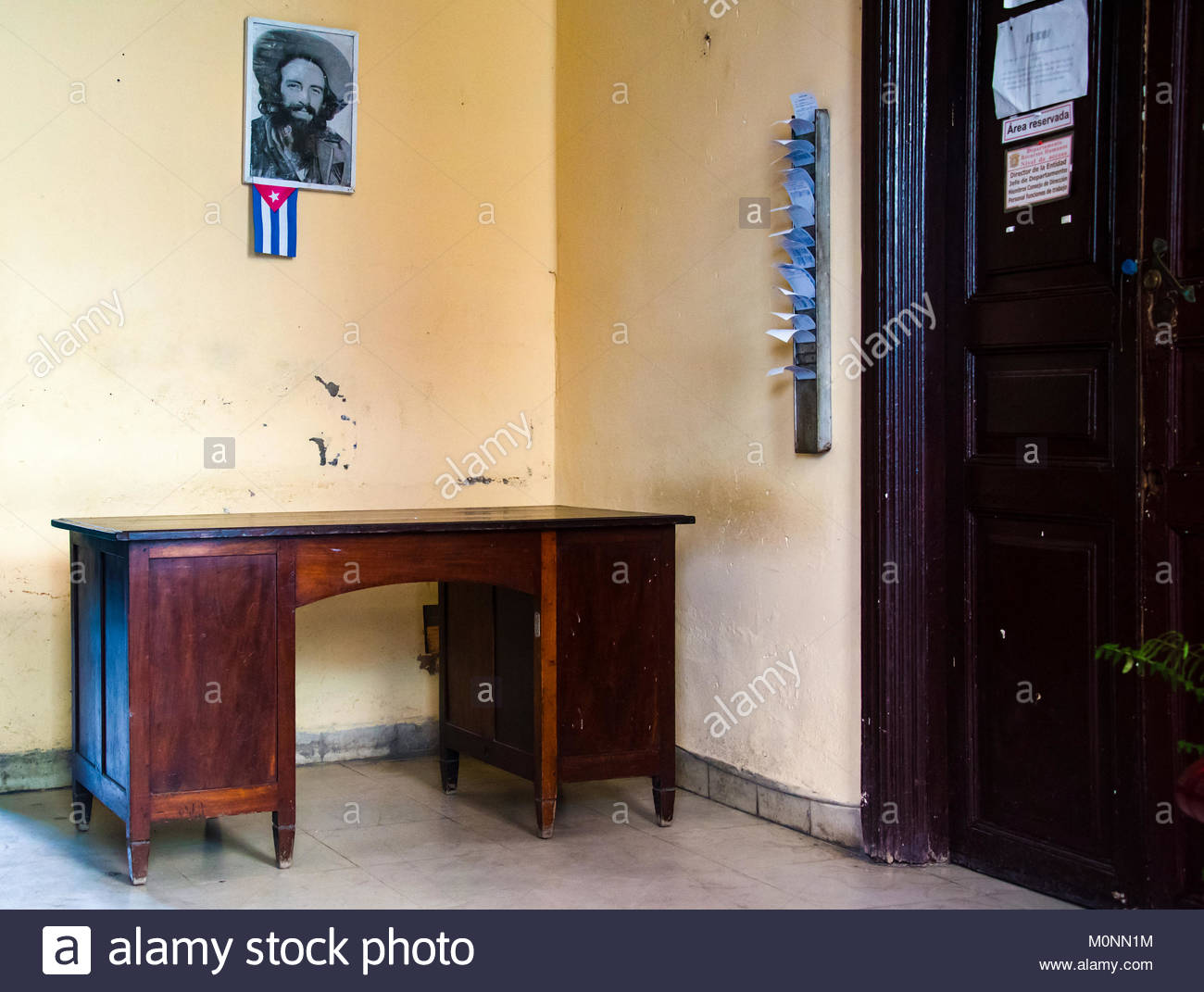 Reception or entrance at a Cuban bureaucratic office. There is a small wooden desk, a picture of Camilo Cienfuegos - Stock Image