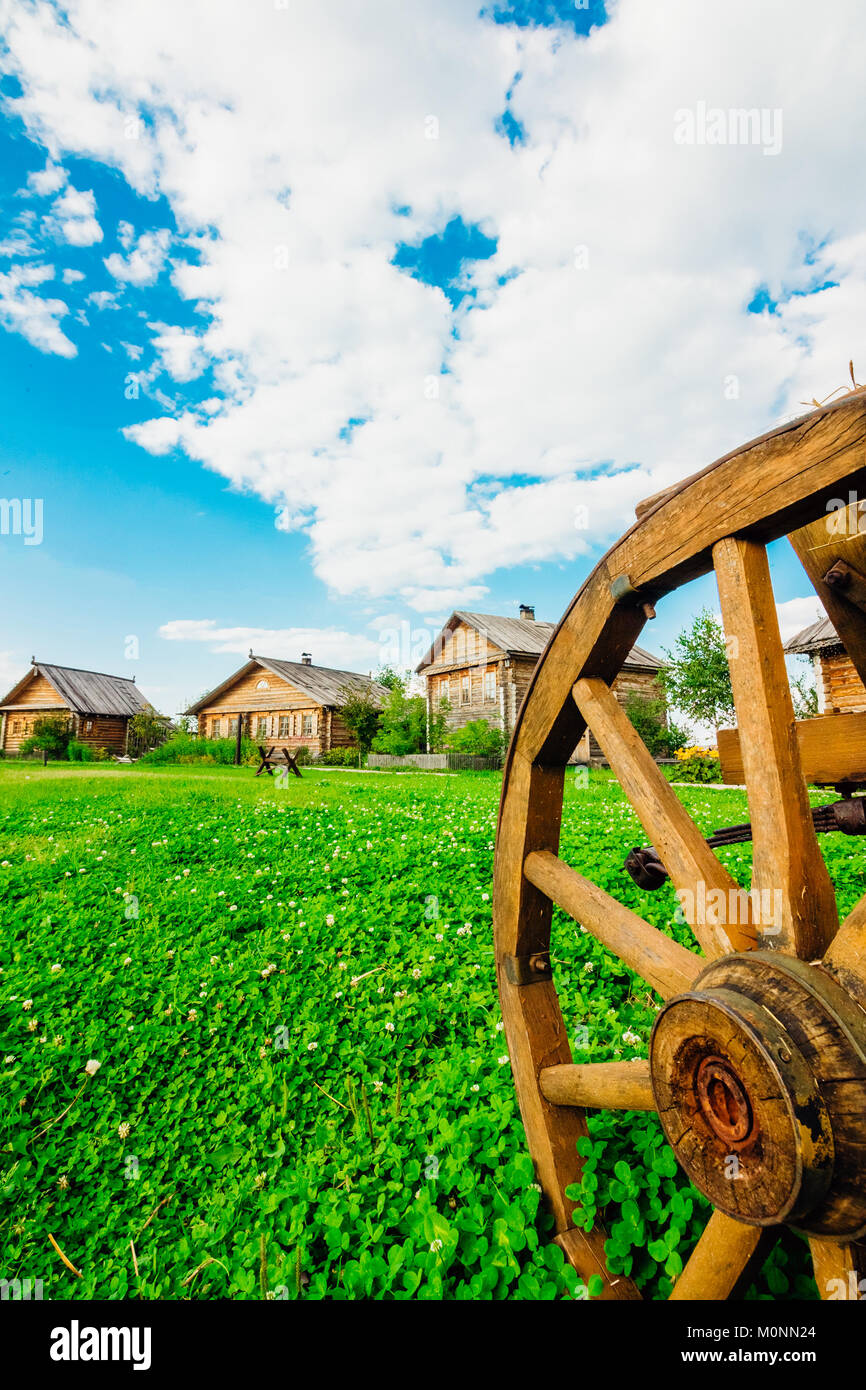 Cartwheel on the green grass. Cabin in the background - Stock Image