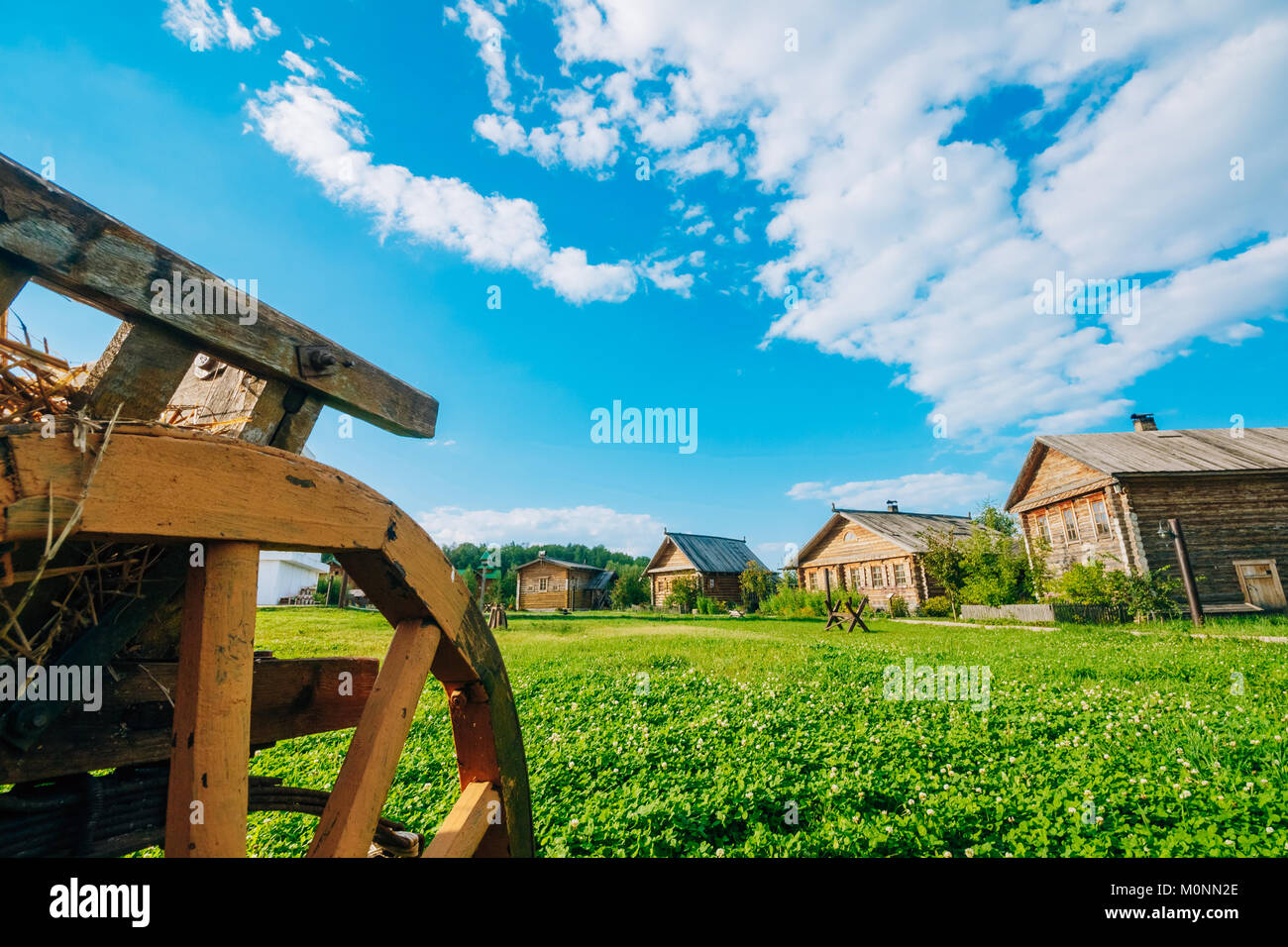 Landscape of countryside with log huts against a beautiful sky with clouds - Stock Image