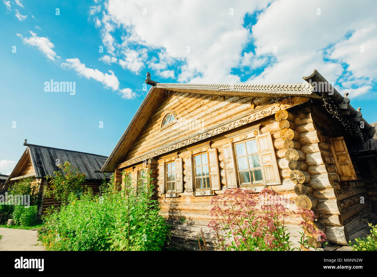 Wooden hut Slavic type on a summer day against the blue bright sky with clouds - Stock Image
