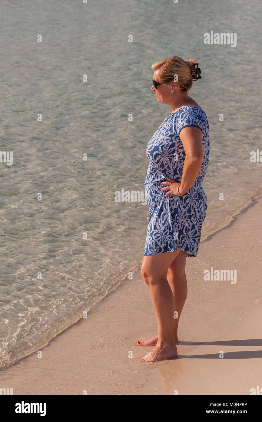 A woman standing on the beach at Punta Prima , Menorca , Balearic Islands , Spain - Stock Image