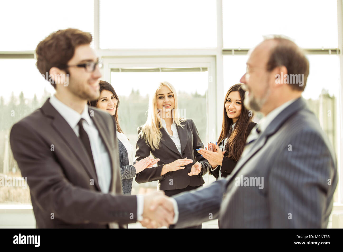 handshake business partners before beginning business negotiations on the background of applauding - Stock Image