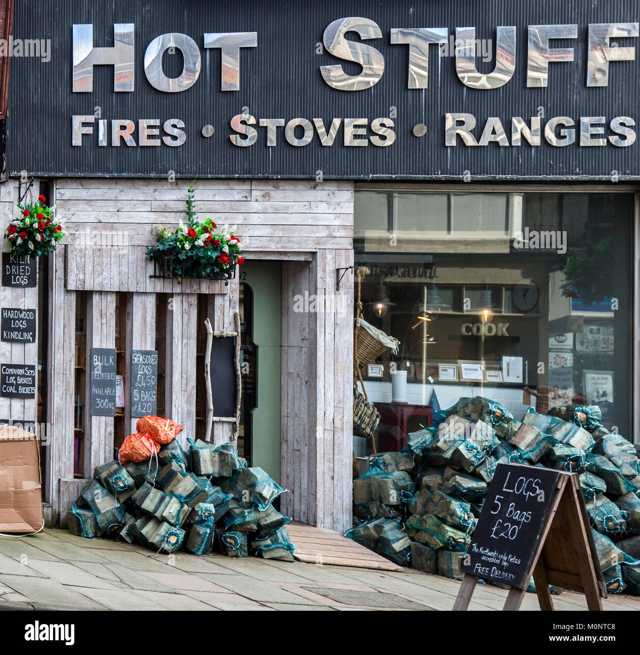 Showroom and store selling Wood Burning Stoves, Ranges, wood, sticks, timber, bagged logs & kindling for open - Stock Image