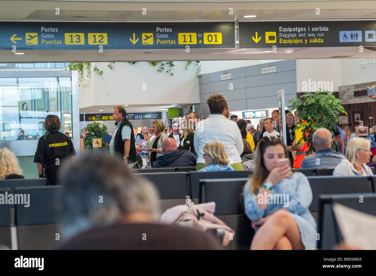 People in a departure lounge at the airport in Mahon , Menorca , Balearic Islands , Spain - Stock Image