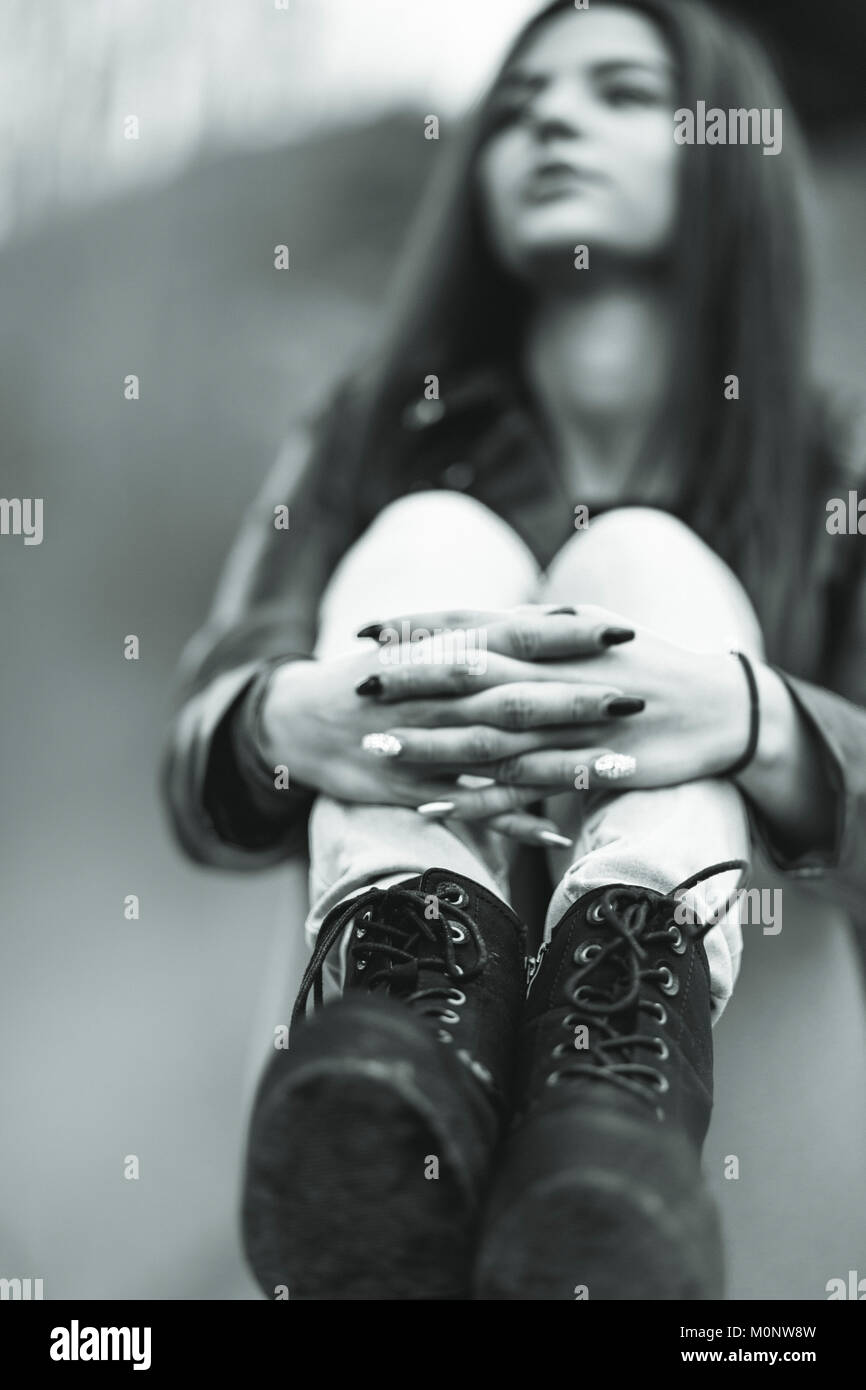 Black and white close up view of a young woman sitting clasping her legs with manicured nails wearing trendy black - Stock Image