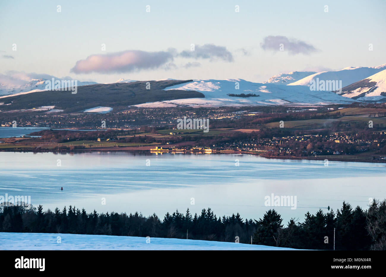 Winter scene across Clyde River to Dumbarton, with snow covered mountains, blue sky and calm glassy water in evening - Stock Image