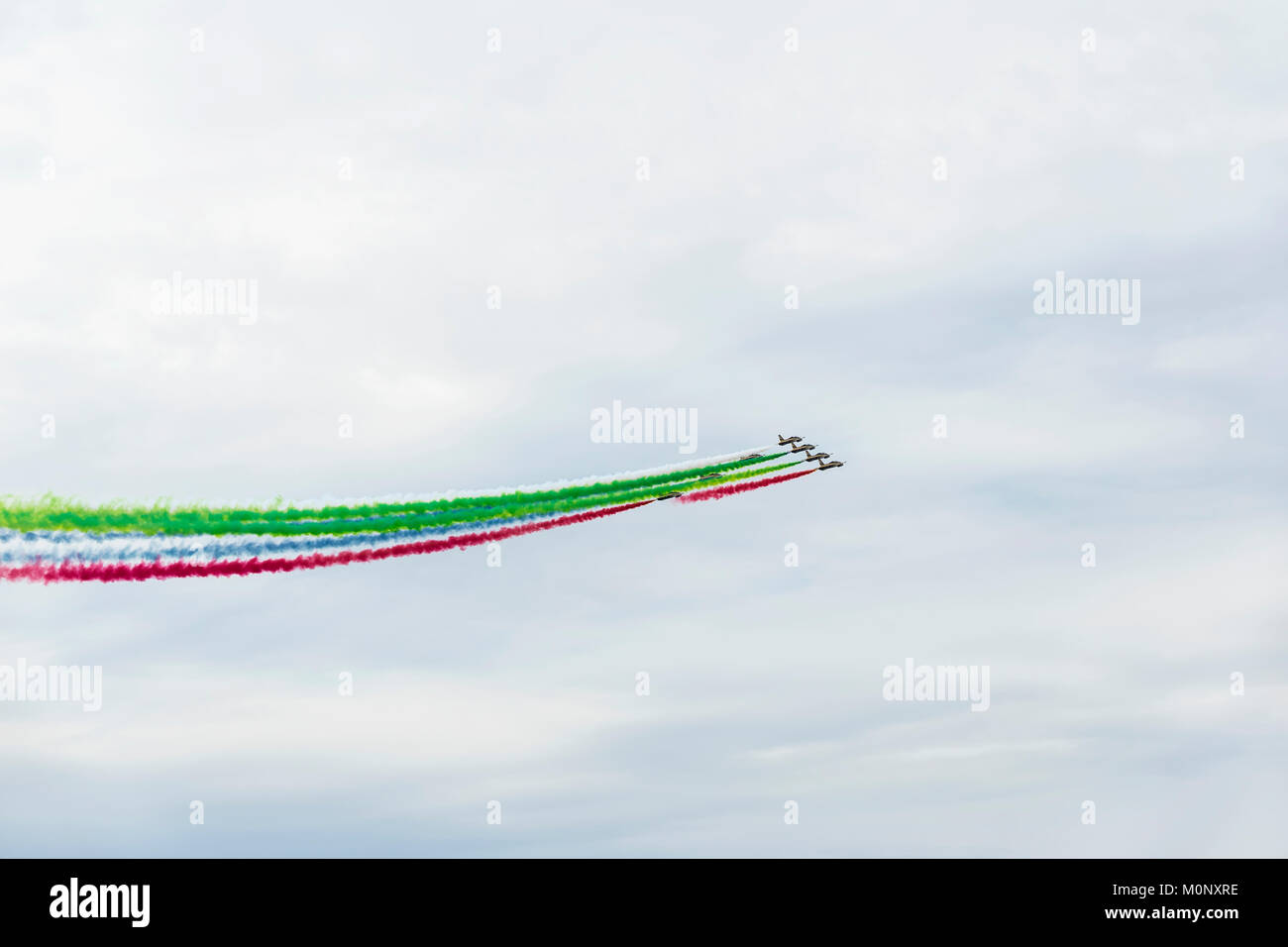 Airplanes on airshow with colorful bright trails of smoke against a blue sky, clouds. Aircraft, flying display and Stock Photo