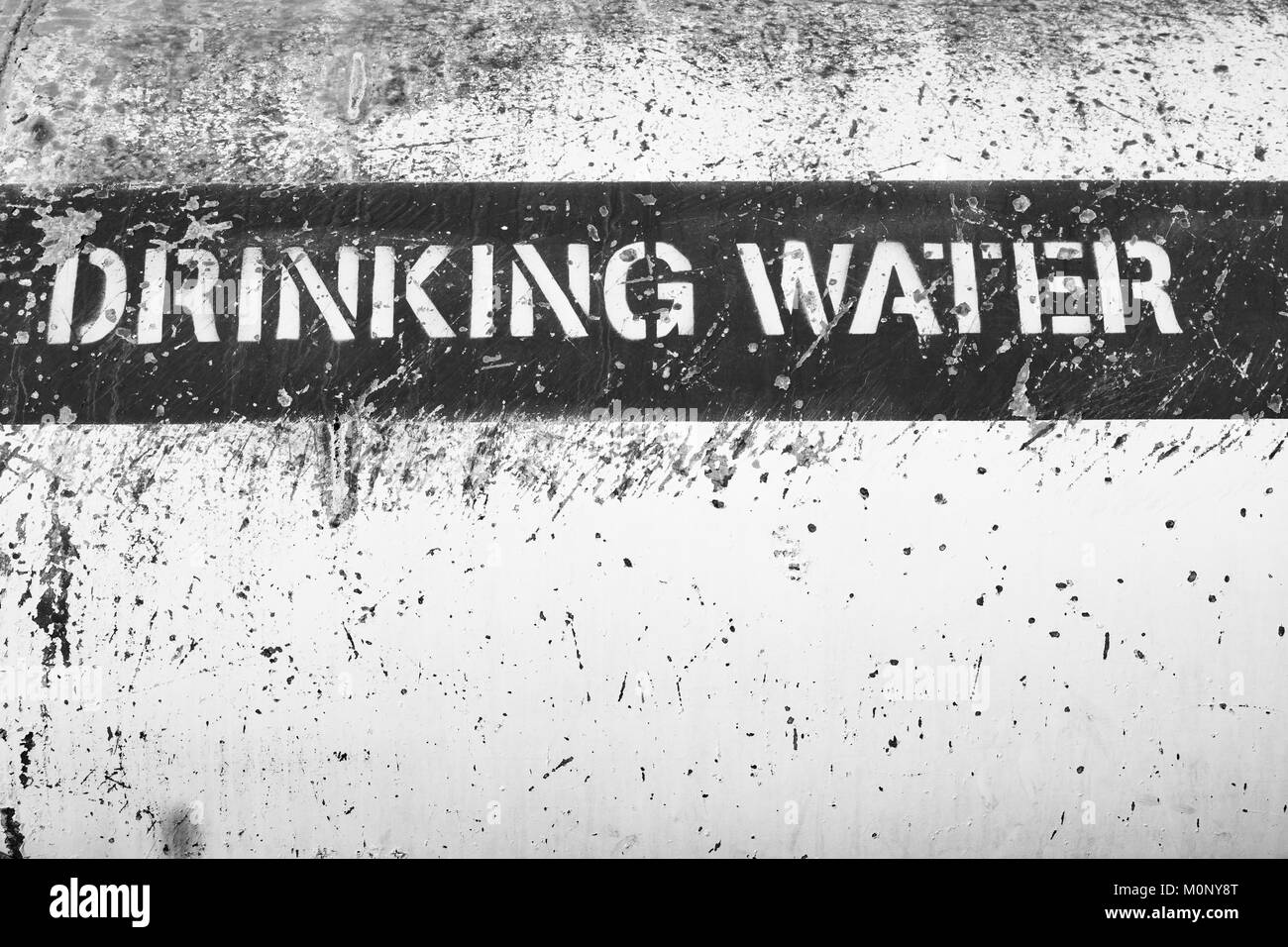 A black and white picture of a label sign saying 'Drinking Water' on the side of a water tanker truck. - Stock Image