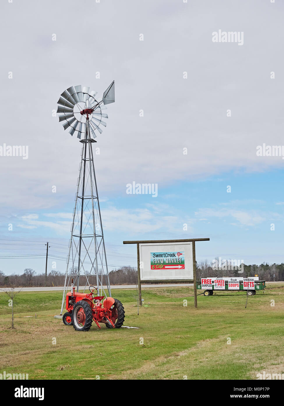 Roadside signs, a red tractor and a windmill water pump advertise a Farm Market in rural Pike Road Alabama, United - Stock Image