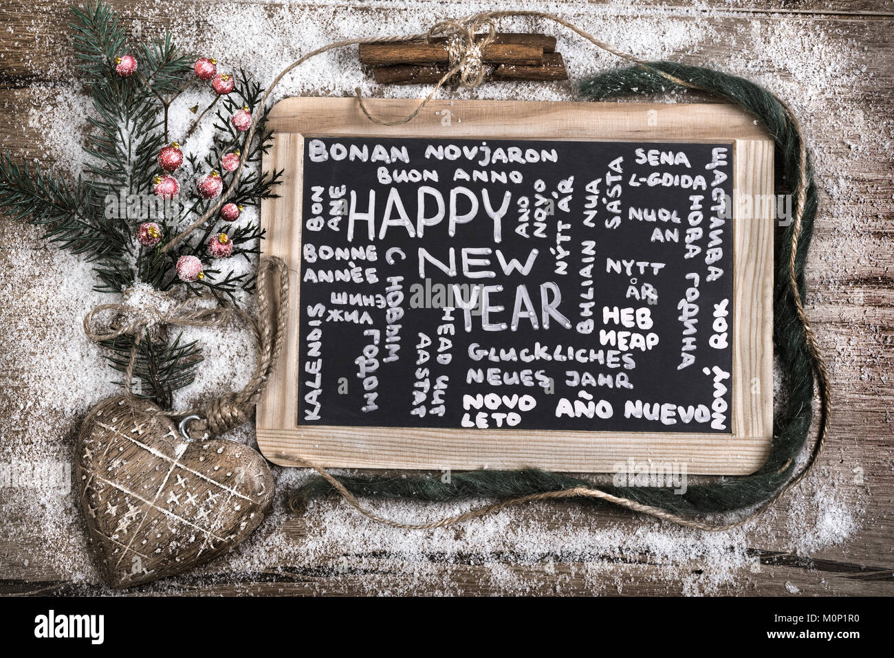 Black charcoal board with caption 'Happy New Year' in many languages among winter decorations - Stock Image