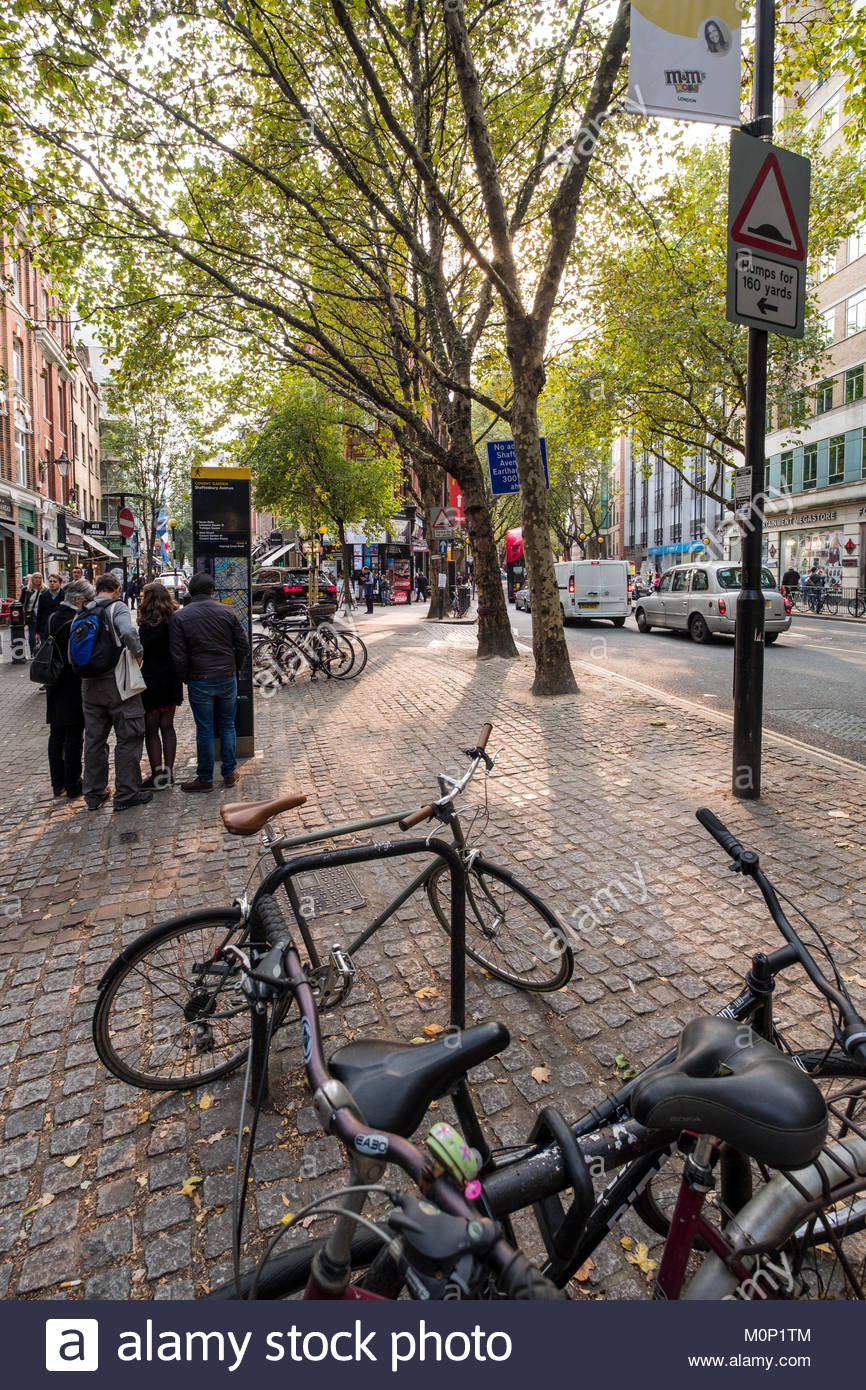 Bicycles parked on cobble stone sidewalk in the shade of London Plane Trees along Shaftesbury Avenue, Camden, London, - Stock Image