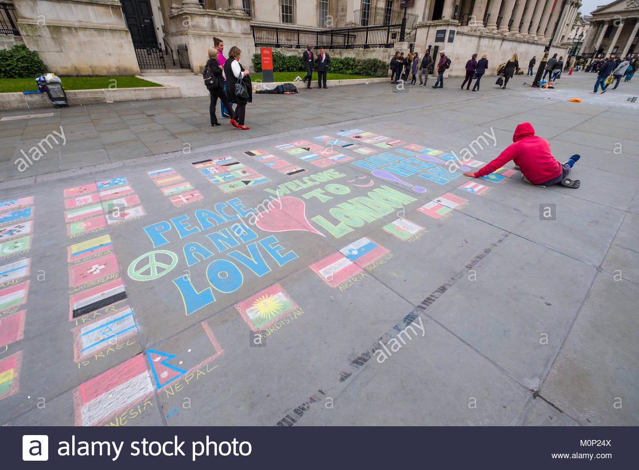 Man using colored chalk to draw flags of various countries on ground of Trafalgar Square, City of Westminster, London, Stock Photo