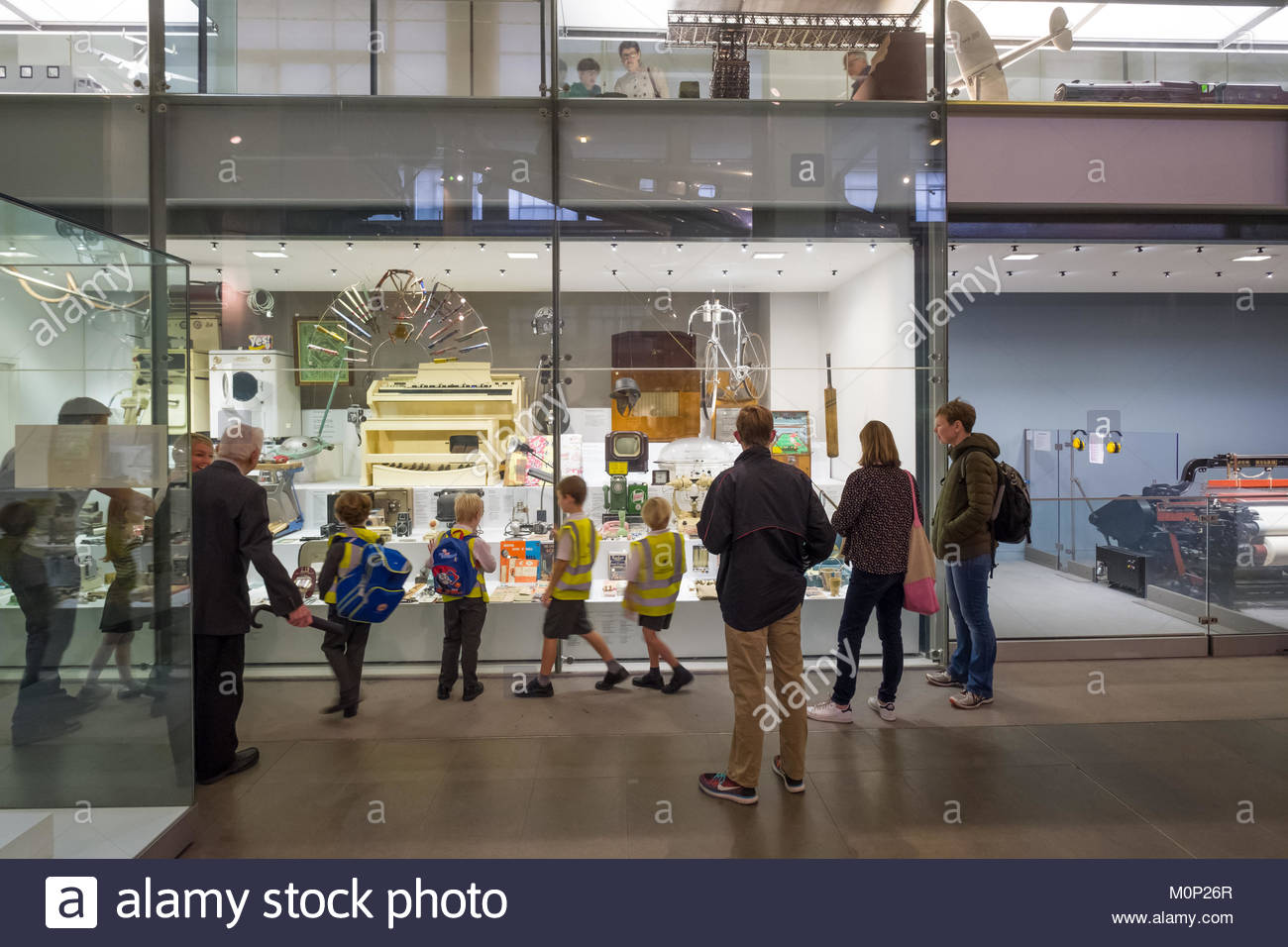 Group of school children looking at display of house hold items from the past 80 years in the Making the Modern - Stock Image