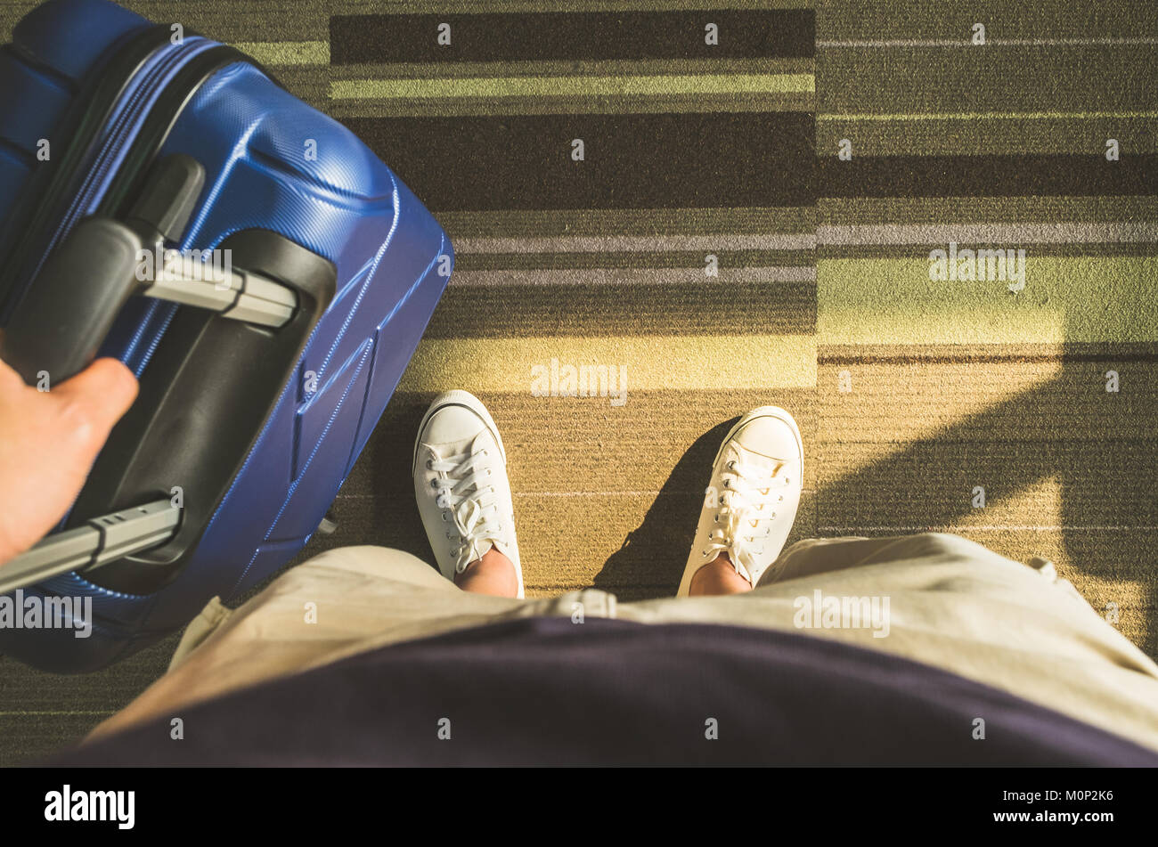 Aerial view,Looking down at white sneaker and travel suitcase with morning sunlight through window at airport terminal,Vacation - Stock Image