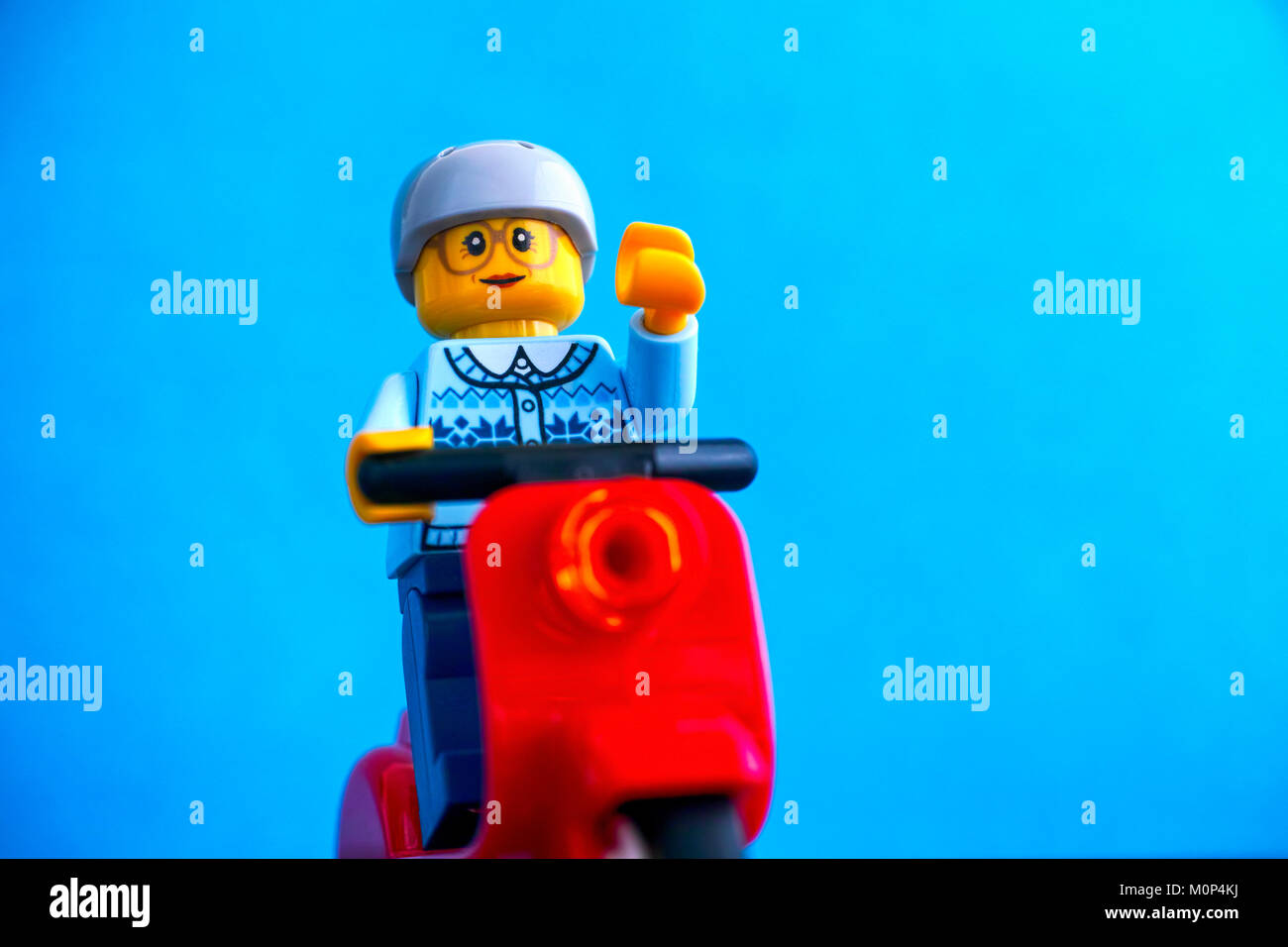 Tambov, Russian Federation - January 13, 2018 Lego old woman minifigure on red scooter. Blue background. Studio - Stock Image