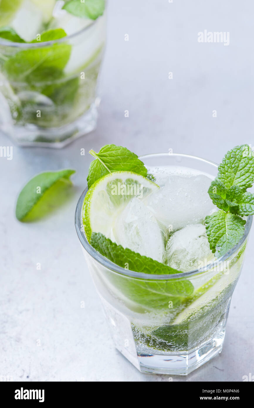 Mojito cocktail, refreshing summer drink in chilled glasses on light gray background - Stock Image