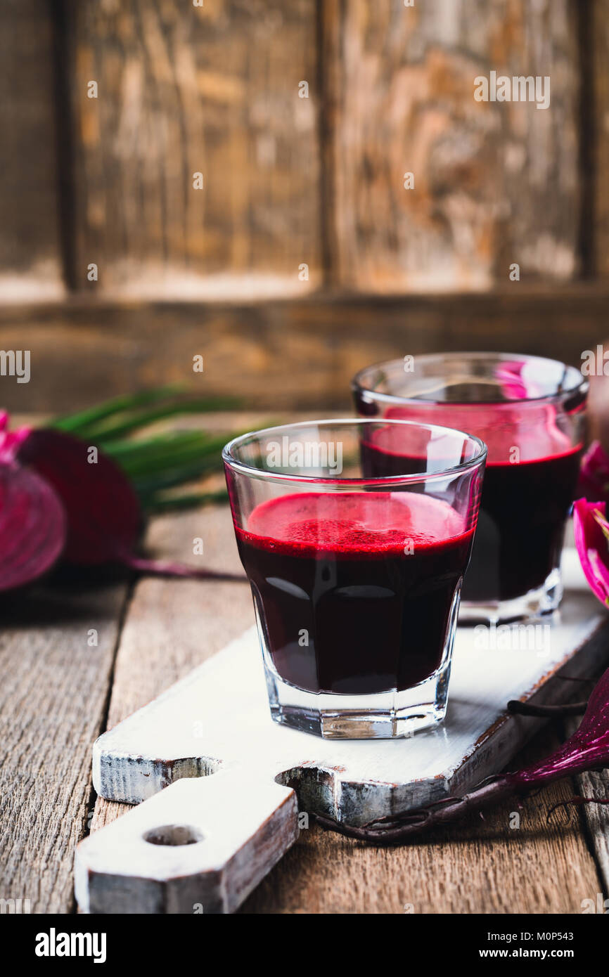 Fresh organic beetroot juice and fresh vegetables on rustic wooden table - Stock Image