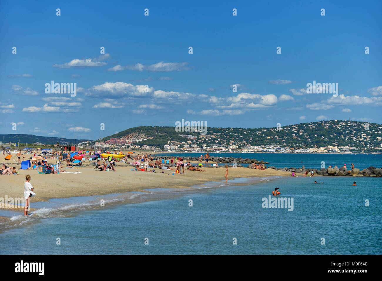 France,Herault,Sete,Beach of Lido,vacationers taking the sun in sea border with Saint Clair Mount in the background - Stock Image