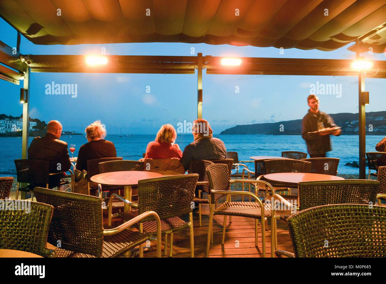 Spain,Girona province,Cadaques,consumers sat under a pergola in the middle of a Café terrace in the face of - Stock Image