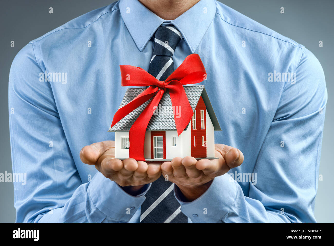 Worker in blue shirt holding house with red ribbon. Close up. Business concept - Stock Image