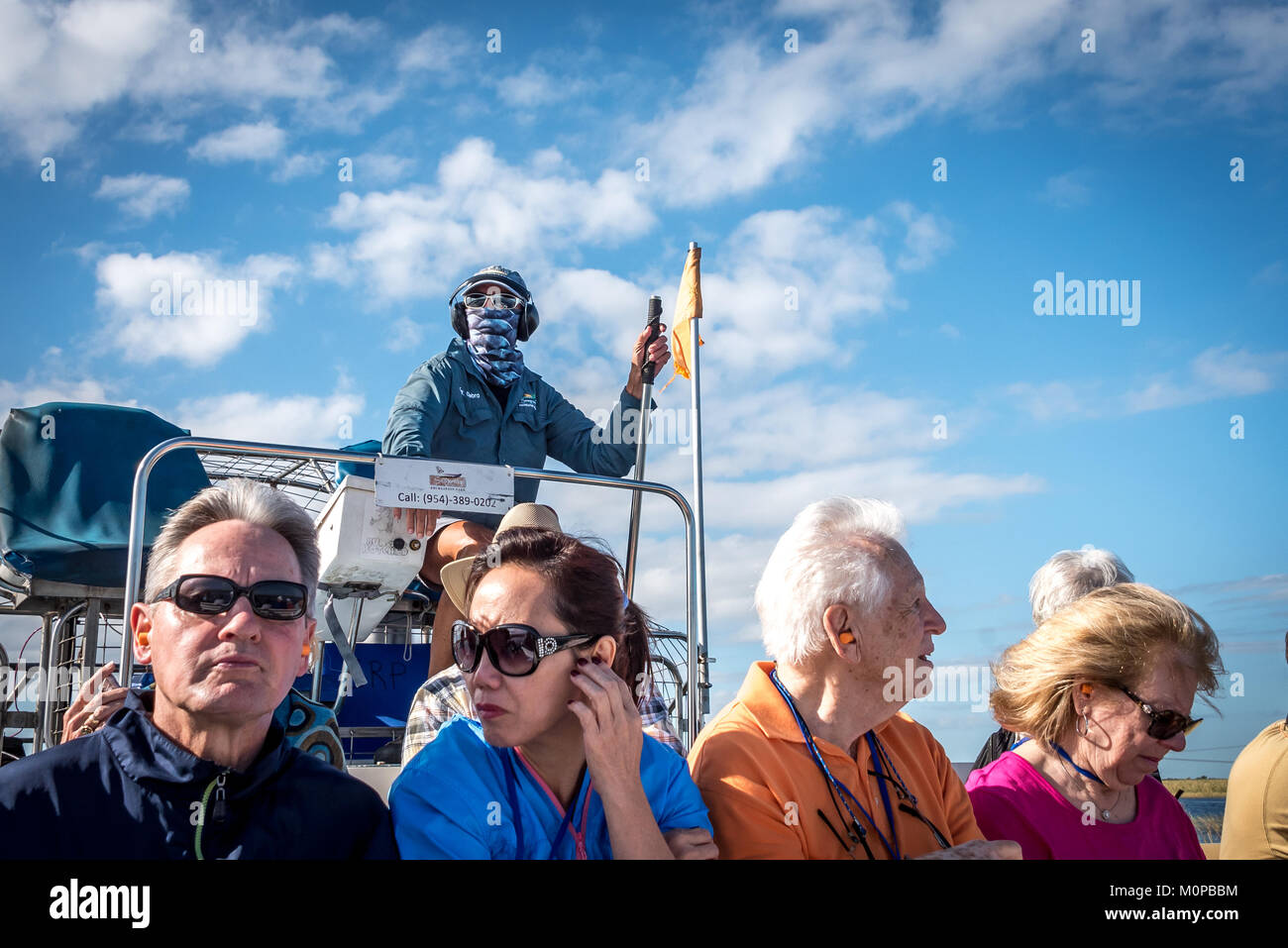 Tourists and captain on airboat in Florida Everglades at Sawgrass Recreation Park (also air boat), looking up captain - Stock Image