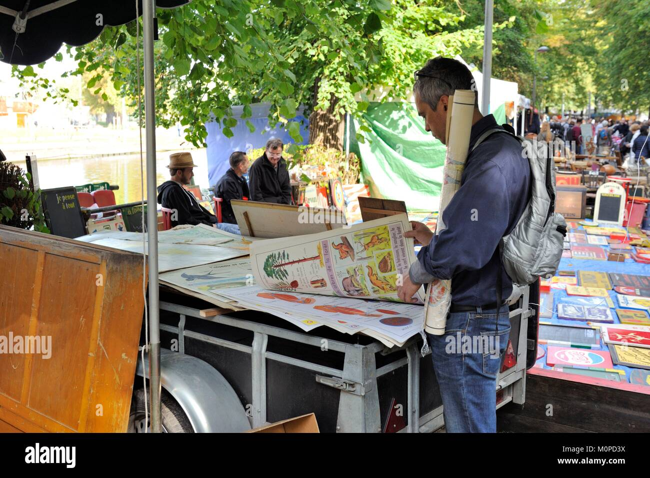 France,Nord,Lille,braderie 2017,secondhand traders along the esplanade,man looking at an old illustration - Stock Image