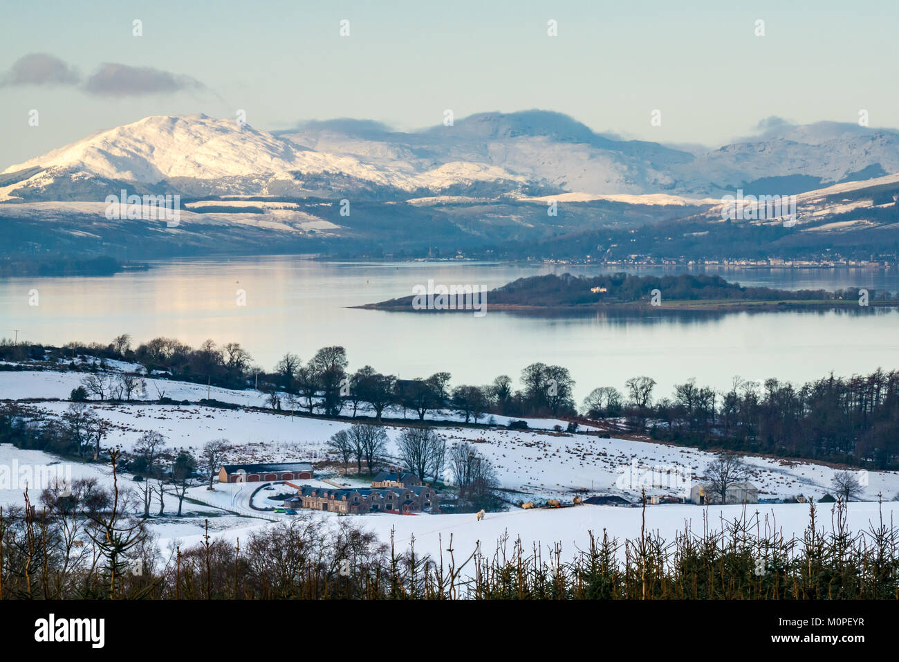 Winter scene across Clyde River from hill above Langbank. Snow covered mountains, blue sky and calm water in evening - Stock Image