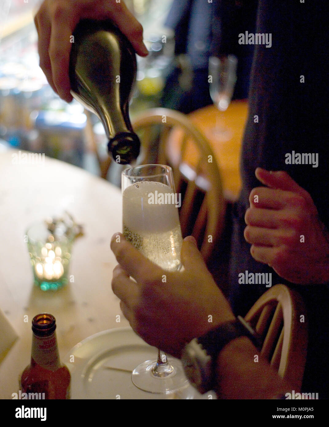 A host pours a glass of champagne for a guest at a birthday party in a west London restaurant, Britain January 22, - Stock Image